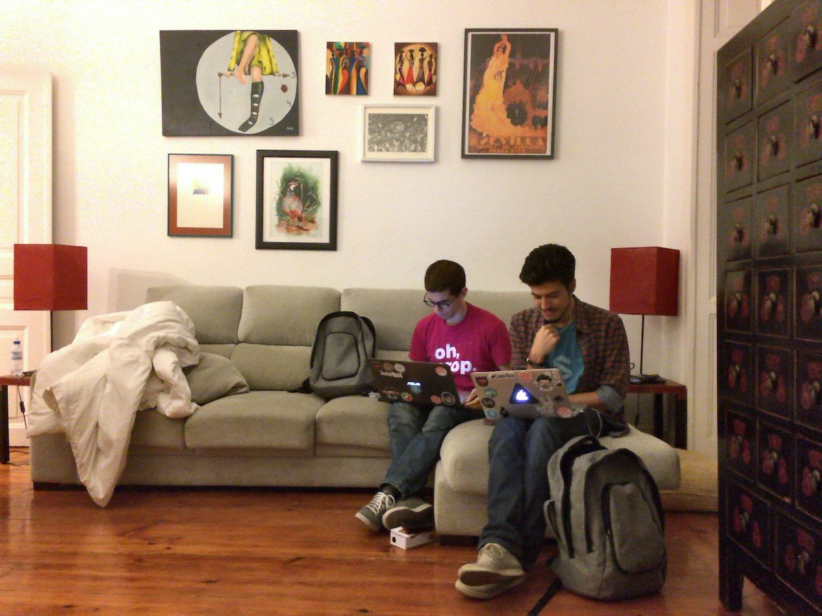 Fernando and Miguel sitting on a couch with their laptops